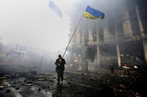 An anti-government protester holds a Ukranian flag as he advances through burning barricades in Kiev