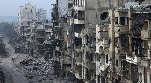 People stand on a street lined with damaged buildings in the besieged area of Homs